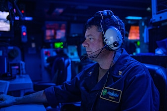 A Sailor stands watch in the combat information center aboard USS O'Kane (DDG 77).