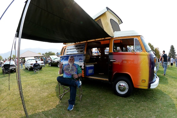 Brian Galligan sits in a chair under the awning of his 1976 Volkswagen Type 2 Campmobile.