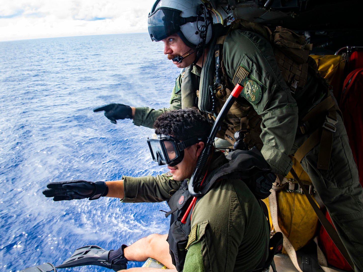 """Naval Aircrewmen (Helicopter) 1st Matthew Brickley from Peoria, Ariz. and Naval Aircrewmen 2nd Class Nicolas Lopez from Artesia, Calif., conducts a search and rescue (SAR) exercise inside of a MH-60S Seahawk helicopter assigned to the """"Blackjacks"""" of Helicopter Sea Combat Squadron (HSC) 21 aboard the Independence-variant littoral combat ship USS Tulsa (LCS 16), Sep. 05, 2021."""