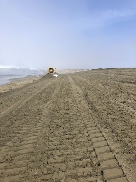 Sloping sand down to water with a bulldozer off in the distance.