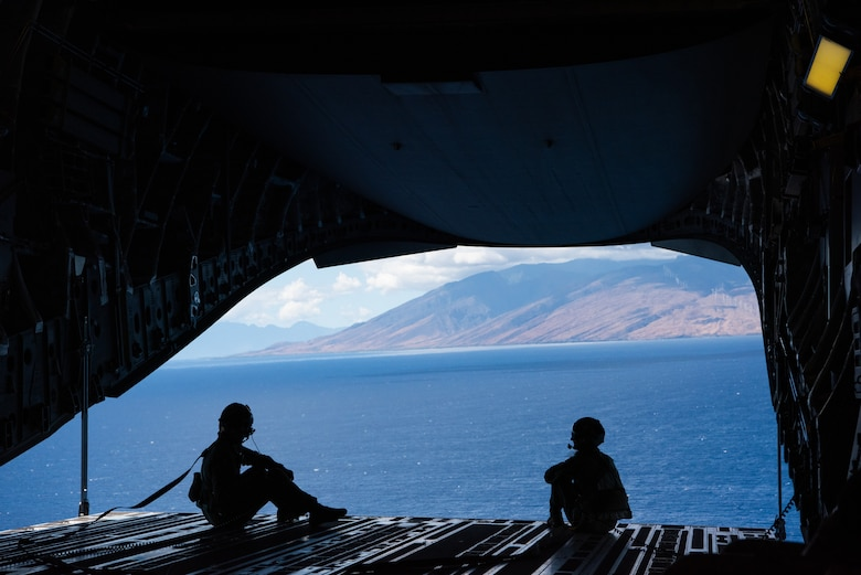 Photo of two Airmen sitting on the back of a C-17 Globemaster III.