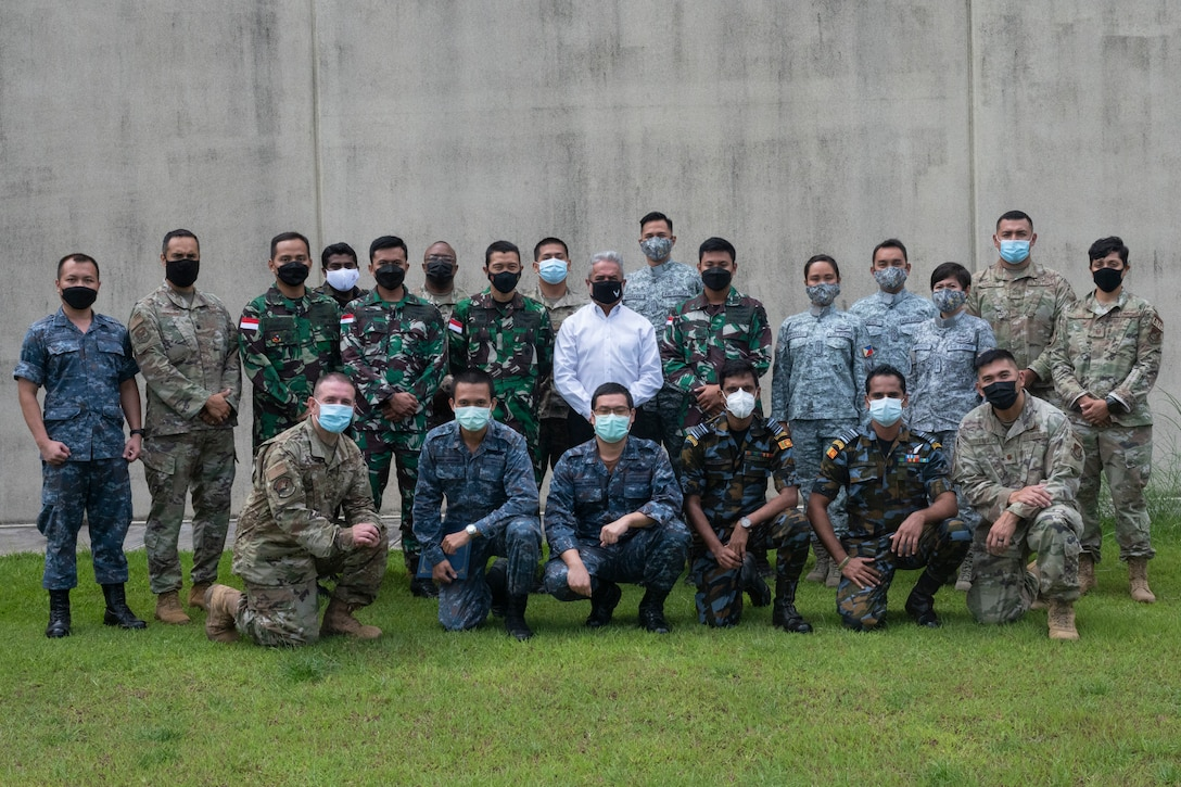 U.S. Air Force instructors from the Inter-American Air Forces Academy pose with international students after the Aircraft Maintenance Officer Course Event graduation ceremony at Andersen Air Force Base, Guam, Aug. 20, 2021.