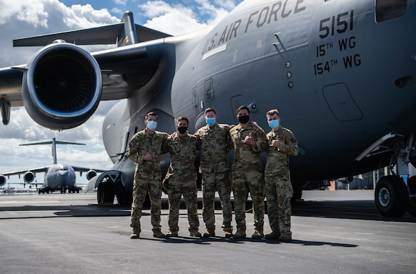 Left to right, Staff Sgt. Garryn Slover, 535th Airlift Squadron loadmaster, 1st Lt. Collin Chow How, 204th Airlift Squadron C-17 Globemaster III copilot, Capt. Steve Brinkley, 535th AS C-17 aircraft commander, 1st Lt. Michael Knab, 535th C-17 copilot, and Airman 1st Class Duke Edens, 535th AS loadmaster, celebrate their return home at Joint Base Pearl Harbor-Hickam, Hawaii, Sept. 7, 2021. After seven days and an estimated 14 hours in-flight, the crew carried out two shuttles supporting evacuation operations in Afghanistan. (U.S. Air Force photo by Senior Airman Alan Ricker)