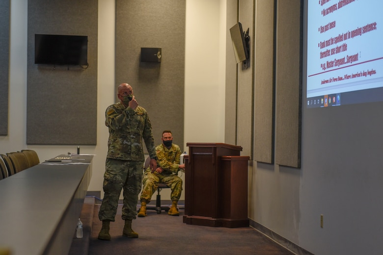 A man standing and presenting power point slides