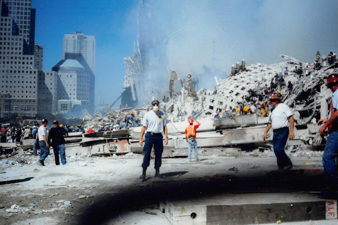 A man stands outside the wreckage at Ground Zero in New York.