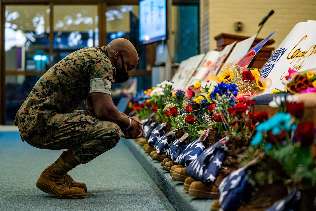 A U.S. Marine mourns at the memorial service for the 13 service members who were killed in action in Kabul, Afghanistan, on Sept. 3, 2021, on Camp Foster, Okinawa, Japan. (U.S. Marine Corps photo by Cpl. Brennan J. Beauton)
