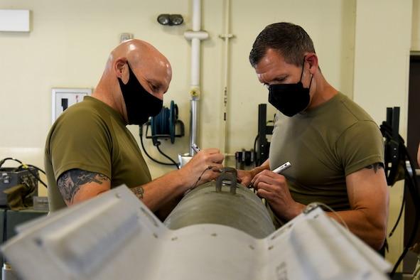 Two Airmen sign a munition.