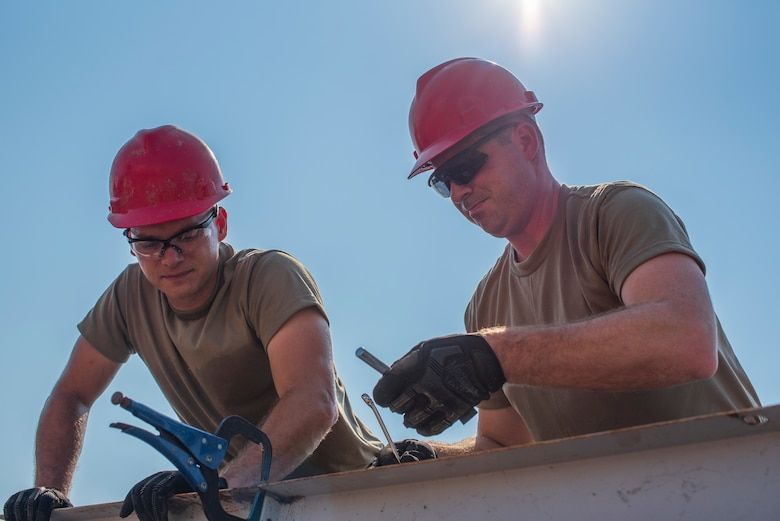 Two men work wearing red hard hats and the Air Force OCP uniform.