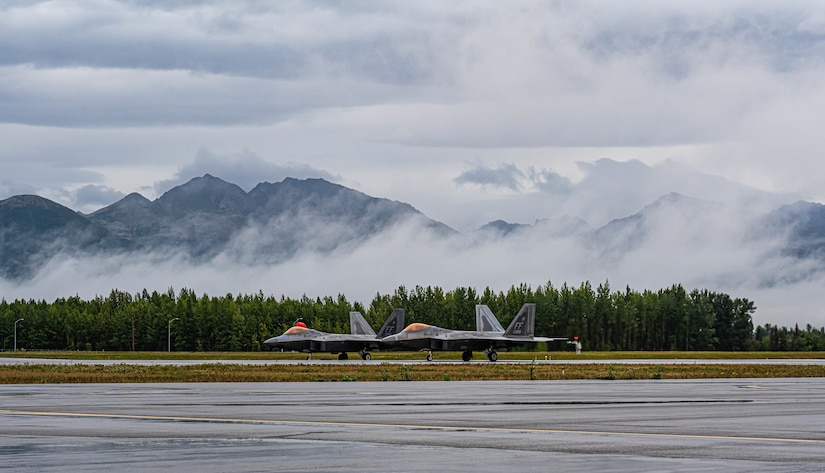 Two jets sit on a runway.