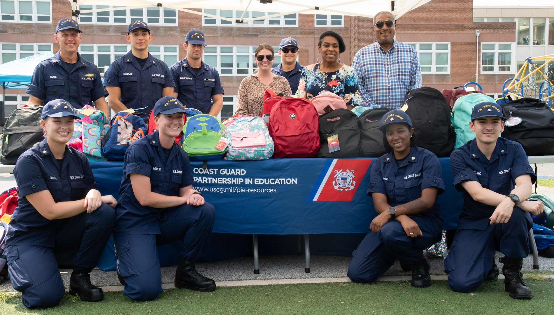 Chaplain Andrew Hoyle (standing, back left), Coast Guard headquarters' Partnership in Education (PIE) coordinator, along with Coast Guard and Department of Homeland Security (DHS) volunteers, pose in front of a table full of backpacks stuffed with school supplies at Anita J. Turner Elementary School during a back-to-school night event, August 26th. Hundreds of Coast Guard and DHS volunteers donated equipment or helped pack backpacks with schools supplies to support the D.C. community through St. Elizabeth's Back-to-School backpack and supply drive (Coast Guard photo by Patrick Ferraris).