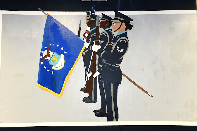 Photo shows a wall painting of four honor guard members carrying flags and rifles