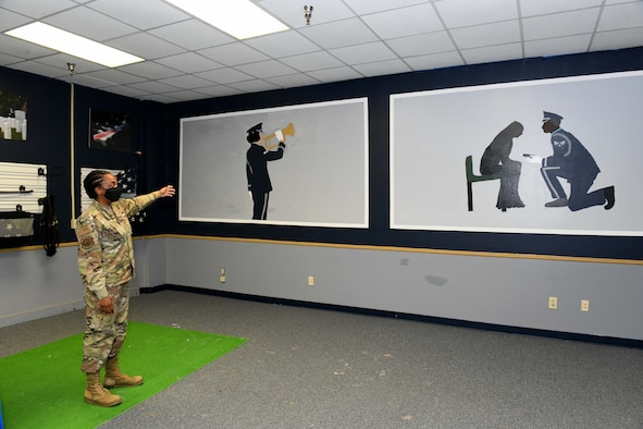 Photo shows woman pointing at two large paintings of the honor guard on the wall.