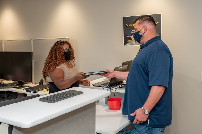 Photo of employee dropping off his computer to a tech.
