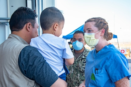 210830-N-OB360-0076 NAVAL AIR STATION SIGONELLA, Italy (Aug. 30, 2021) Lt. j.g. Katherine Harbaugh, a Kokomo Ind. native and nurse assigned to Navy Medicine Readiness and Training Command San Diego assesses the needs of an evacuee from Afghanistan aboard Naval Air Station Sigonella, Aug. 27, 2021. NAS Sigonella is currently supporting the Department of State mission to facilitate the safe departure and relocation of U.S. citizens, Special Immigration Visa recipients, and vulnerable populations from Afghanistan. (U.S. Navy photo by Chief Mass Communication Specialist Ben Farone)