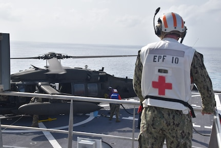 210823-N-N3764-0100 CARIBBEAN SEA - (Aug. 23, 2021) – Hospital Corpsman 3rd Class Jordan Huff, assigned to the Spearhead-class expeditionary fast transport ship USNS Burlington (T-EPF 10) stands ready to assist in case of an  emergency during the refueling of a U.S. Army UH-60 Blackhawk helicopter on the flight deck, Aug. 23, 2021. Burlington is deployed to U.S. Naval Forces Southern Command/ U.S. 4th Fleet to support humanitarian assistance and disaster relief (HADR) efforts in Haiti following a 7.2-magnitude earthquake on Aug. 14, 2021. (U.S. Navy photo by Chief Intelligence Specialist Taylor Hart /Released)