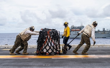 Marines embarked aboard the amphibious assault ship USS Essex (LHD 2) move cargo on the flight deck during a replenishment-at-sea.