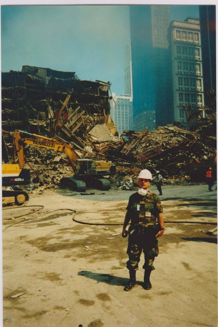 """New York Army National Guard Maj. Edward Keyrouze assists at the still smoldering """"rubble pile"""" at Ground Zero following the attack on the World Trade Center towers in New York Sept. 11, 2001. More than 14,000 members of the New York National Guard responded to the attack."""