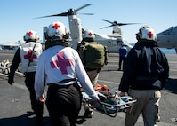 210222-N-SS900-1006 PACIFIC OCEAN (Feb. 22, 2021) Medical personnel carry a simulated patient during a medical transport drill on the flight deck of Nimitz-class nuclear aircraft carrier USS Carl Vinson (CVN 70). The drill was the first-ever medevac by a Navy CMV-22B Osprey aboard an aircraft carrier. Vinson is currently underway conducting routine maritime operations. (U.S. Navy photo by Mass Communication Specialist 3rd Class Aaron T. Smith/Released)