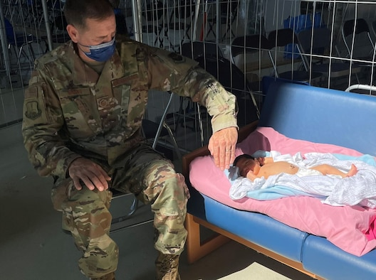 U.S. Air Force Master Sgt. Steve Brooks, 117th Air Refueling Wing religious affairs airman, shields a three-day-old baby's eyes from the sun September 3, 2021, at Ramstein Air Base, Germany. The baby, born to Afghan evacuee parents at Landstuhl Regional Medical Center, received phototherapy for a case of jaundice at the 521st Air Mobility Operations Wing's Hangar 5 prior to boarding a flight. Brooks is a Religious Affairs Airman from the Alabama National Guard serving at Ramstein Air Base, Germany in support of Operation Allies Refuge. (U.S. Air Force courtesy photo)