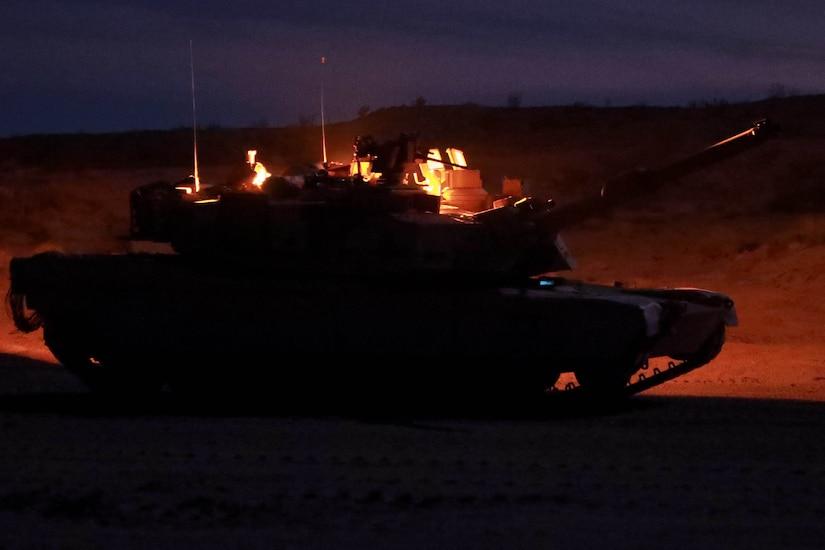 A tank sits on a range at night.