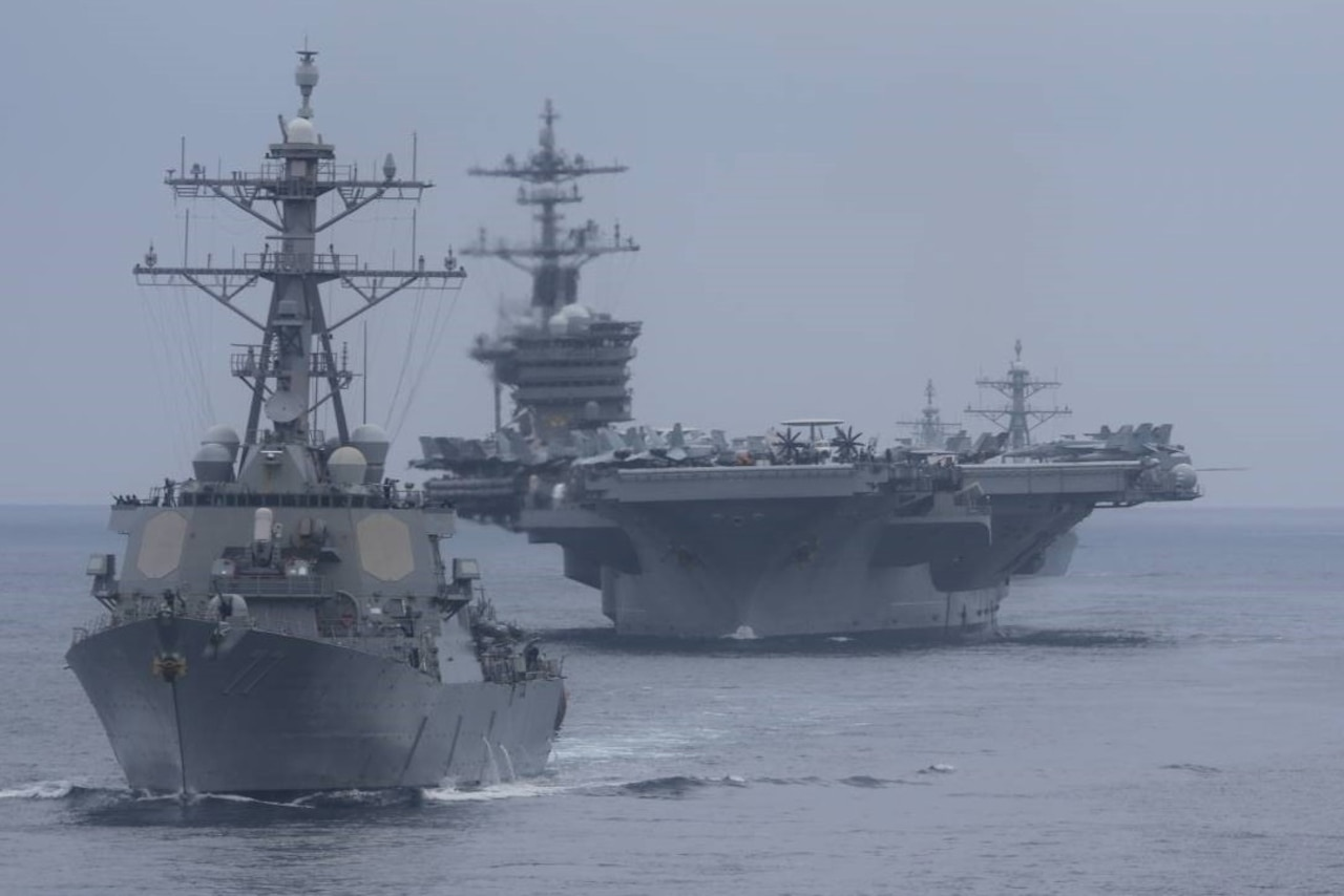Large military ships move through the ocean.