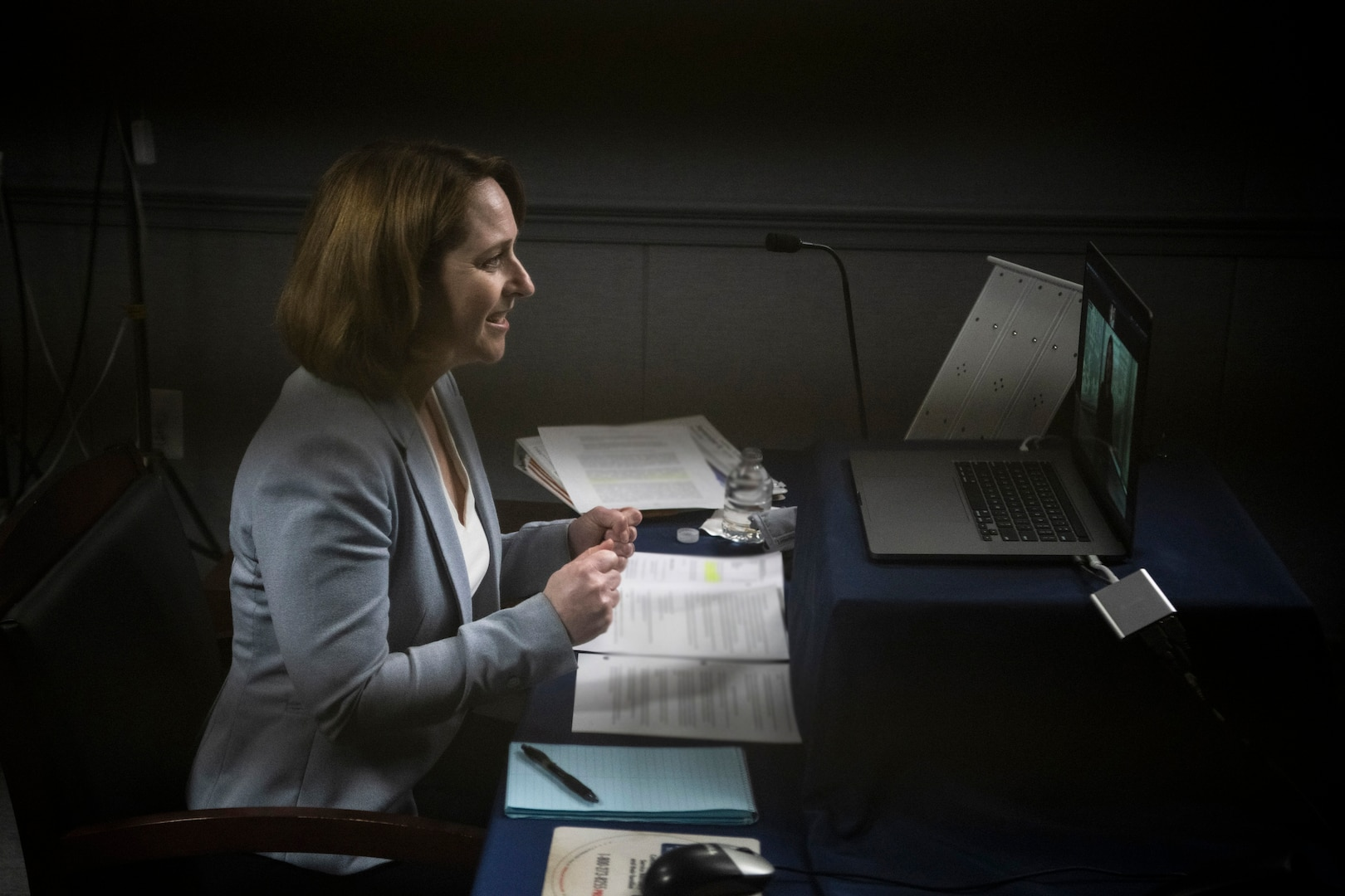 Deputy defense secretary sits at a table and speaks in front of a computer screen.