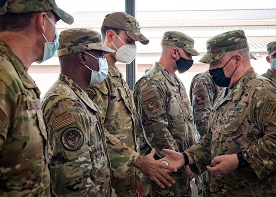 Photo of U.S. Army Gen. Mark Milley, right, the 20th Chairman of the Joint Chiefs of Staff, coining Airmen at Joint Base McGuire-Dix-Lakehurst.