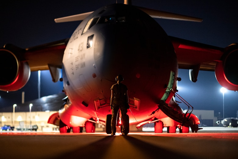 Photo of an Airman standing in front of an aircraft at night