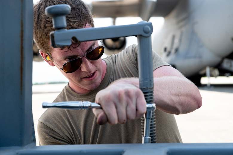 Photo of an Airman using a wrench