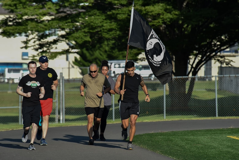 Five participants run on a track, while the right most member holds up the POW/MIA flag up above his shoulder.