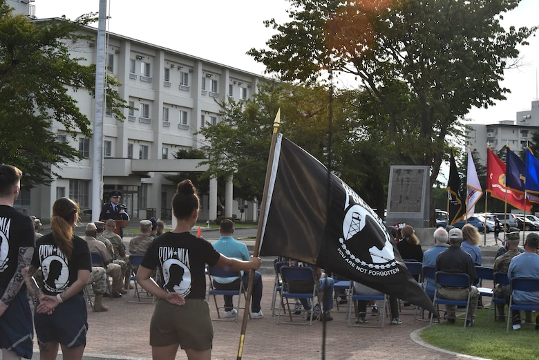 Members stand at parade rest while the guidon bearer holds the POW/MIA flag