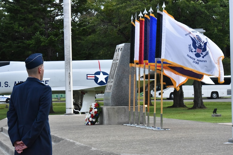 A man in uniform stands in front of flags, flowers and a memorial stone.