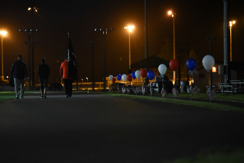 Members hold up the POW/MIA flag in a track at night.