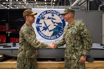 Vice Adm. Brad Cooper, left, commander of U.S. Naval Forces Central Command, U.S. 5th Fleet and Combined Maritime Forces, shakes hands with Capt. Michael D. Brasseur, the first commodore of Task Force (TF 59) during a commissioning ceremony for TF 59 onboard Naval Support Activity Bahrain, Sept. 9. TF 59 is the first U.S. Navy task force of its kind, designed to rapidly integrate unmanned systems and artificial intelligence with maritime operations in the U.S. 5th Fleet area of operations.