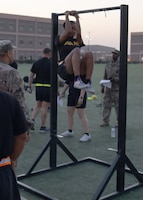 Sgt. Britteny Walton, deployed to Camp Arifjan, Kuwait, with the Fort Bragg, N.C., based 3rd Expeditionary Sustainment Command, executes the leg tuck during the unit's Sept. 7, 2021, Army Combat Fitness Test familiarization event. Walton said she focused on improving her score on the leg tuck by making it part of her workout routine, as well as, stopping to perform one or two leg tucks, whenever she walks around the camp and comes upon a leg tuck iron bar.