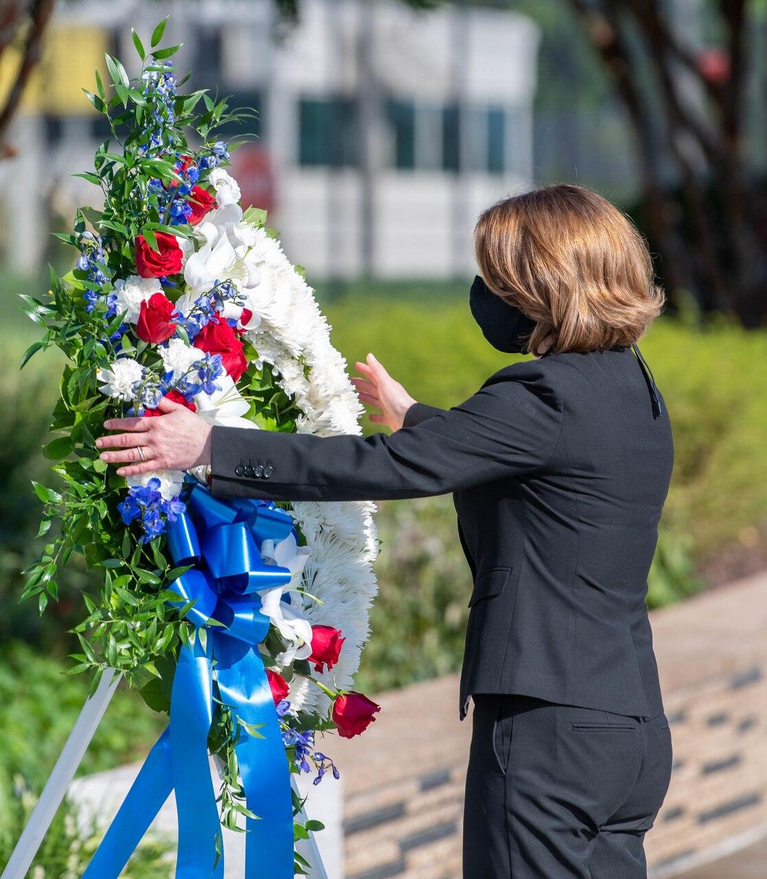 A woman lays a wreath at a memorial.