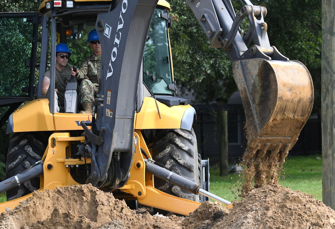 U.S. Air Force Col. William Hunter, 81st Training Wing commander, operates a backhoe with the assistance of Staff Sgt. Chase Kiefer, 85th Engineering Installation Squadron cable and antenna systems technician, during an 85th EIS immersion tour behind Maltby Hall at Keesler Air Force Base, Mississippi, Sept. 1, 2021. The purpose of the tour was to become more familiar with the squadron's mission and its capabilities. (U.S. Air Force photo by Kemberly Groue)