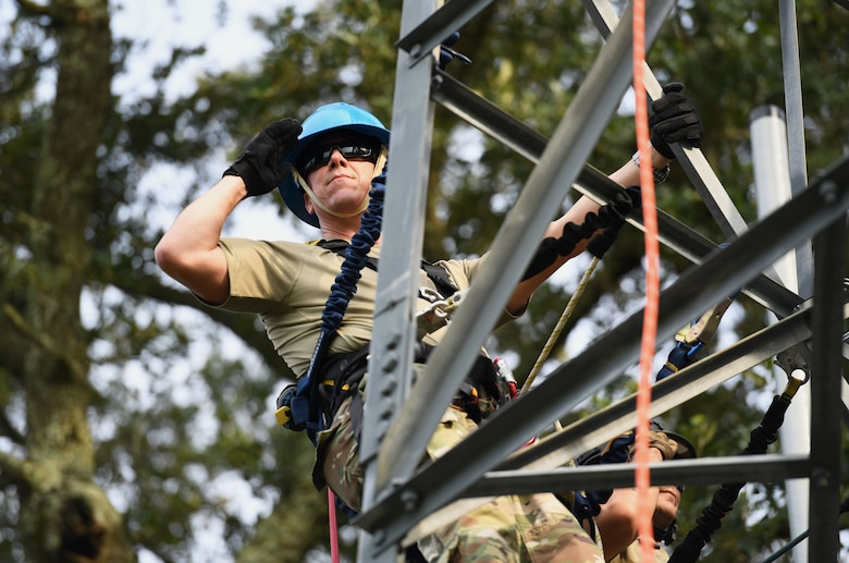 U.S. Air Force Col. William Hunter, 81st Training Wing commander, renders a salute during the playing of the national anthem while participating in a tower climbing demonstration during an 85th Engineering Installation Squadron immersion tour behind Maltby Hall at Keesler Air Force Base, Mississippi, Sept. 1, 2021. The purpose of the tour was to become more familiar with the squadron's mission and its capabilities. (U.S. Air Force photo by Kemberly Groue)