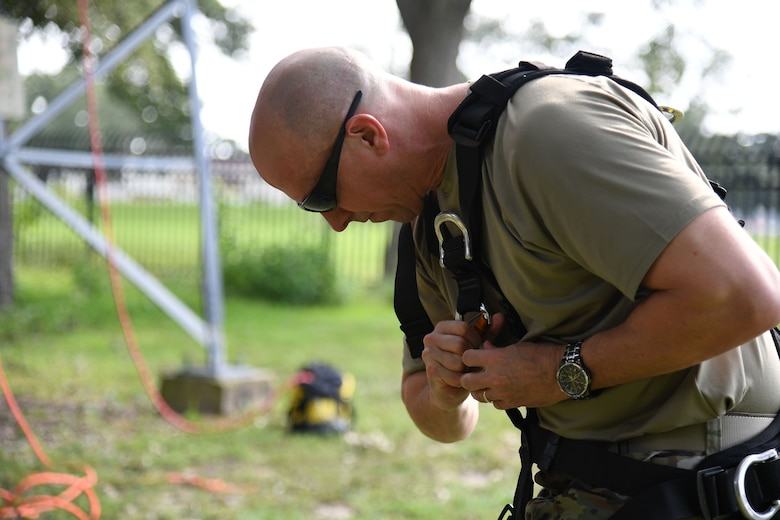 U.S. Air Force Col. William Hunter, 81st Training Wing commander, secures his equipment prior to participating in a tower climbing demonstration during an 85th Engineering Installation Squadron immersion tour behind Maltby Hall at Keesler Air Force Base, Mississippi, Sept. 1, 2021. The purpose of the tour was to become more familiar with the squadron's mission and its capabilities. (U.S. Air Force photo by Kemberly Groue)