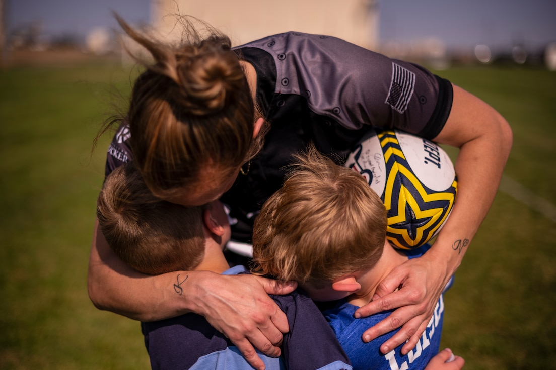 A standing woman holds her sons with her arms while a rugby ball is tucked away in her arms as well.