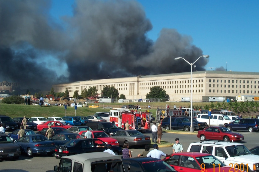 Smoke emanates from a burning building. Firetrucks are in a parking lot.