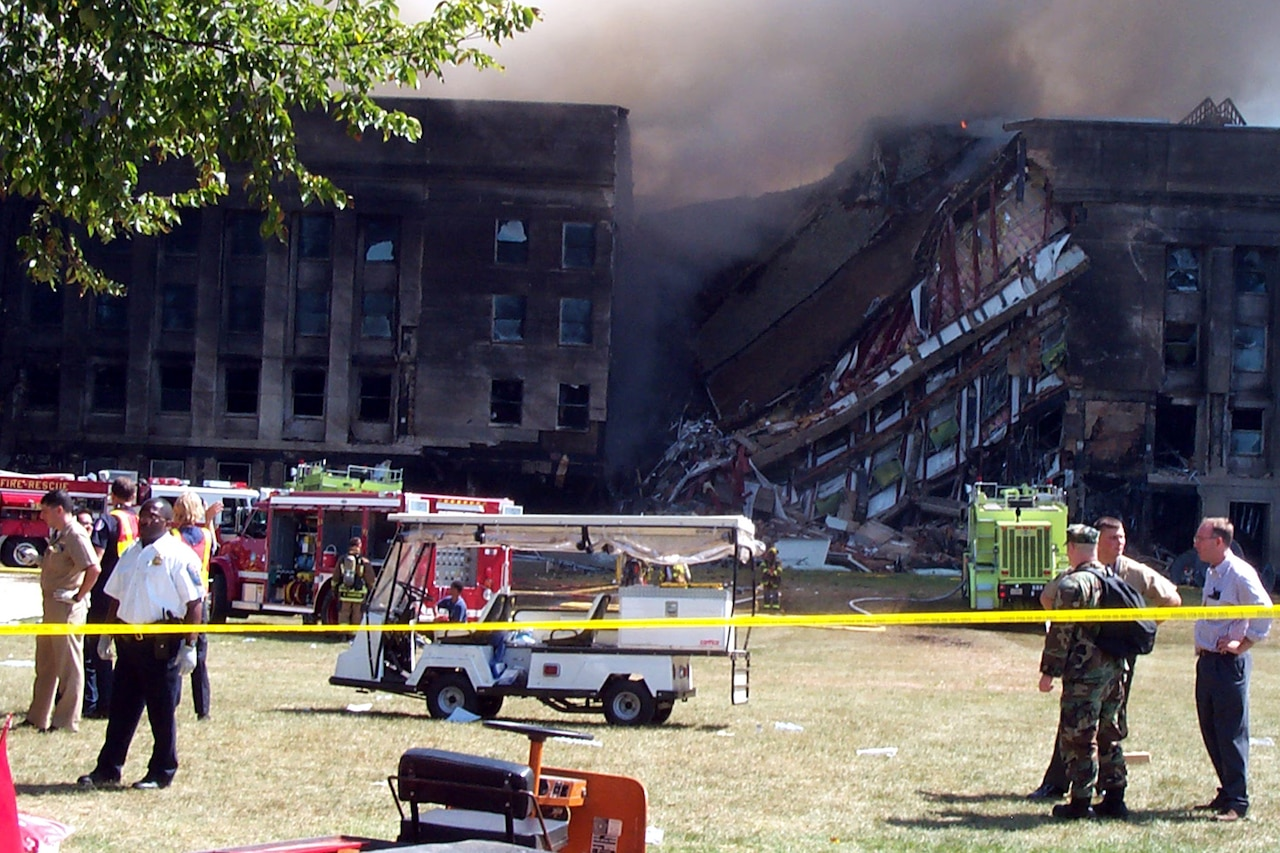 A collapsed building is shown. Smoke rises.