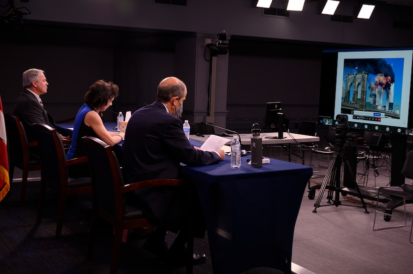 In a studio setting, three individuals sit at a table and look at a computer monitor.