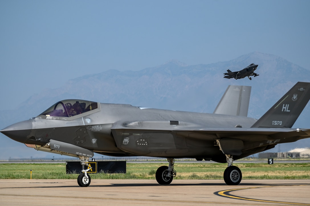 An F-35A Lightning II assigned to 388th Fighter Wing at Hill lands as another F-35A from the 63rd Fighter Squadron at Luke Air Force Base takes off Aug. 25, 2021, at Hill Air Force Base, Utah. The 63rd FS was participating in a Weapons System Evaluation Programs, known as Combat Hammer and Combat Archer, which tests and validates the performance of crews, pilots, and their technology while deploying air-to-air and air-to-ground munitions. (U.S. Air Force photo by Cynthia Griggs)