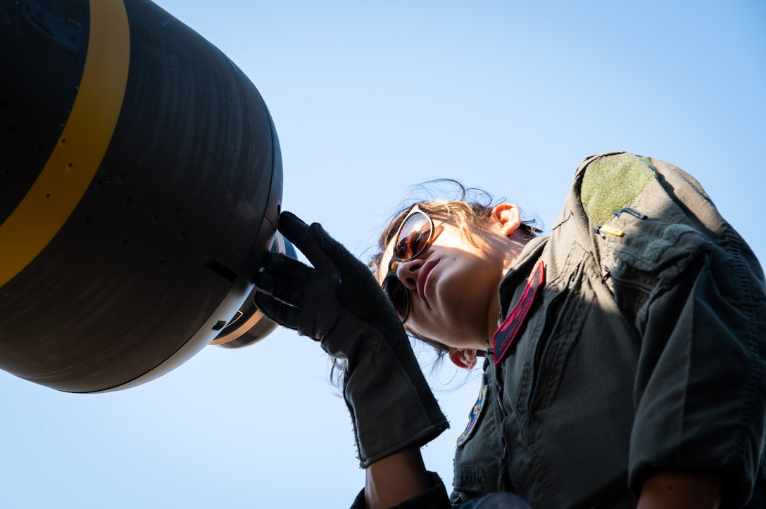 First Lt. Victoria Gurrola, 96th Bomb Squadron weapon systems officer, inspects a CBU-105 conventional munition before takeoff at Barksdale Air Force Base, Louisiana, Aug. 25, 2021. CBU-105s are multi-targeting bombs capable of destroying numerous armored targets in a single drop. (U.S. Air Force photo by Airman 1st Class Chase Sullivan)