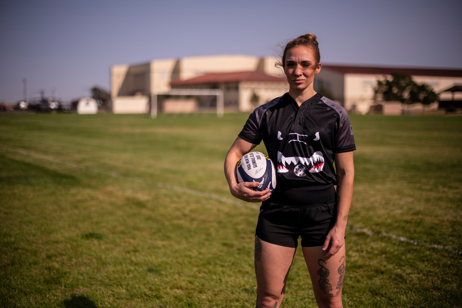 A woman stand on a soccer field holding a rugby ball.