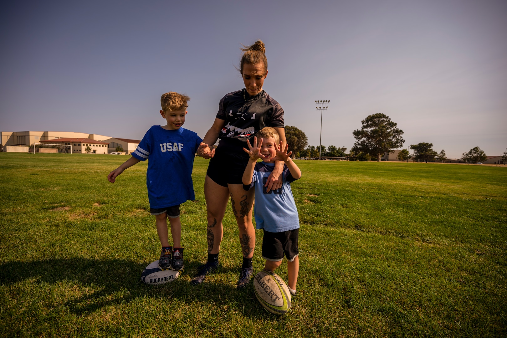 A woman stands with her two young boys on a soccer field while they hold rugby balls.