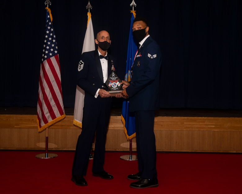 Military members in uniform pose with an award for a photo