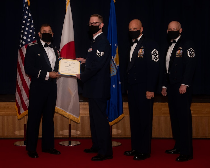 Military members in uniform pose with a diploma for a photo