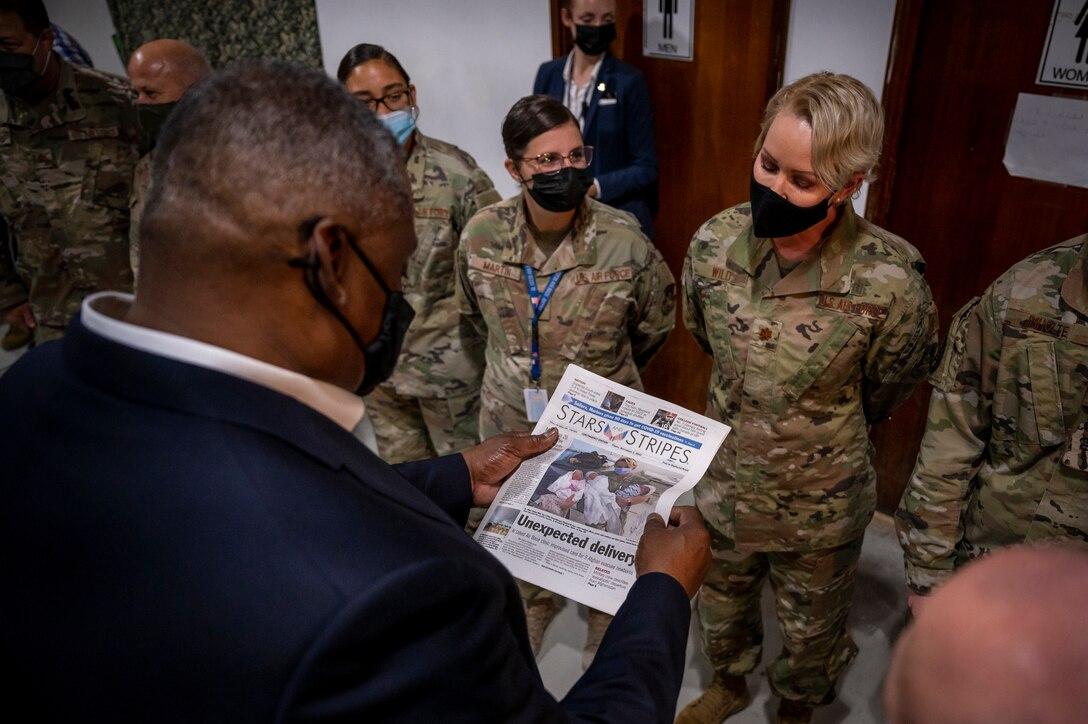 Secretary of Defense Lloyd J. Austin III looks at a newspaper highlighting service members who supported Afghanistan evacuation operations Sept. 07, 2021, at Al Udeid Air Base, Qatar.